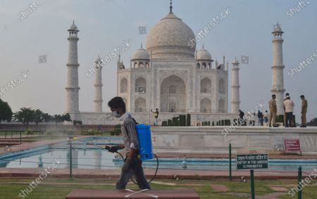 Man disinfects the premises of the Taj Mahal monument that was reopened after being closed for more than six months due to the coronavirus pandemic in Agra, India, Monday, Sept.21, 2020