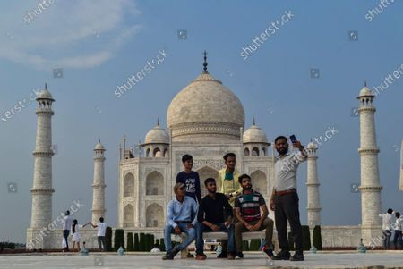 Group of Indian tourists pose for photographs in-front of the Taj Mahal monument that was reopened after being closed for more than six months due to the coronavirus pandemic in Agra, India, Monday, Sept.21, 2020