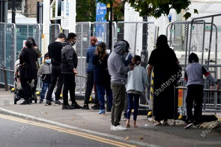 Members of the public queue at an NHS testing facility in Edmonton, London, Britain, 21 September 2020. It is reported that British Prime Minister Boris Johnson is considering possible further restrictions after a rise in COVID-19 cases in the UK.