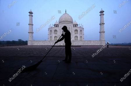 Man sweeps at the Taj Mahal monument early morning in Agra, India, Monday, Sept.21, 2020. The Taj Mahal reopened Monday after being closed for more than six months due to the coronavirus pandemic