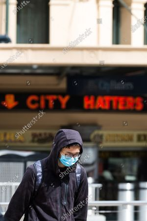 A man wearing a facemask walks across the street during COVID-19 in Melbourne, Australia.  Victoria recorded only 11 new cases overnight and two deaths, despite this Premier Daniel Andrews continues to refuse to ease restrictions. Meanwhile Melbournians are suffering lockdown fatigue, businesses are closing and mental health is suffering an upsurge.
