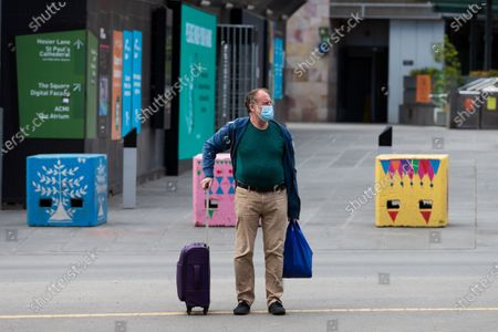 A man with a suitcase waits for traffic before he crosses the street during COVID-19 in Melbourne, Australia.  Victoria recorded only 11 new cases overnight and two deaths, despite this Premier Daniel Andrews continues to refuse to ease restrictions. Meanwhile Melbournians are suffering lockdown fatigue, businesses are closing and mental health is suffering an upsurge.