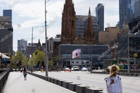 A woman is seen walking by as the wind blows her hair over her face during COVID-19 in Melbourne, Australia.  Victoria recorded only 11 new cases overnight and two deaths, despite this Premier Daniel Andrews continues to refuse to ease restrictions. Meanwhile Melbournians are suffering lockdown fatigue, businesses are closing and mental health is suffering an upsurge.