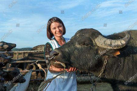 Head of the Karpatskyi buivil (Carpathian Buffalo) farm Inna Levdar stays by a buffalo near Vynohradiv, Zakarpattia Region, western Ukraine.