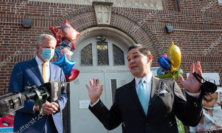 New York City Schools Chancellor Richard Carranza, right, talks at a news conference at the Mosaic Pre-K Center while Mayor Bill de Blasio, left, listens on the first day of school, in New York. The city public schools delayed reopening for two weeks