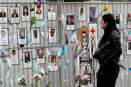 A woman walks past a makeshift memorial to medical workers that have died from COVID-19, in front of the local health department in central St. Petersburg, Russia, 21 September 2020. In the past 24 hours Russia registered 6,196 new cases caused by the SARS-CoV-2 coronavirus infection and 71 coronavirus-related deaths.
