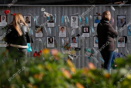 Two people view a makeshift memorial to medical workers that have died from COVID-19, in front of the local health department in central St. Petersburg, Russia, 21 September 2020. In the past 24 hours Russia registered 6,196 new cases caused by the SARS-CoV-2 coronavirus infection and 71 coronavirus-related deaths.