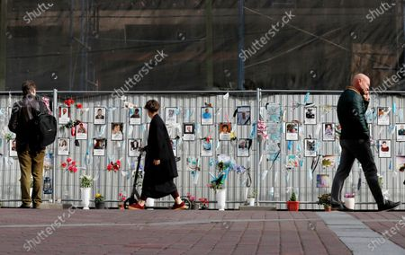 People walk past a makeshift memorial to medical workers that have died from COVID-19, in front of the local health department in central St. Petersburg, Russia, 21 September 2020. In the past 24 hours Russia registered 6,196 new cases caused by the SARS-CoV-2 coronavirus infection and 71 coronavirus-related deaths.