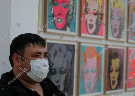 A worker wearing face mask stands in front of 'Marilyn Monroe' artworks by US Pop artist Andy Warhol during installation exhibition 'Me, Andy Warhol', at New Tretyakov Gallery in Moscow, Russia, 21 September 2020. The exhibit, which features 200 artworks, will run from 25 September to 10 January 2021.