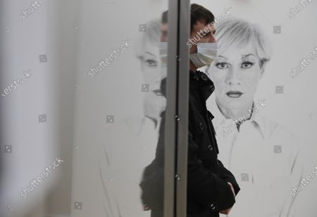 A worker wearing face mask stands in front of pictures of Andy Warhol by US photographer Christopher Makos, during installation of the exhibition 'Me, Andy Warhol', at New Tretyakov Gallery in Moscow, Russia, 21 September 2020. The exhibit, which features 200 artworks, will run from 25 September to 10 January 2021.