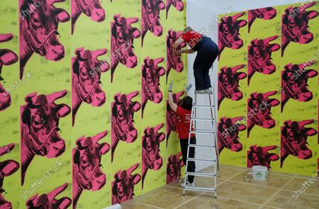 Worker sticks Andy Warhol's Cow Wallpaper during installation of an exhibition 'Me, Andy Warhol', at New Tretyakov Gallery in Moscow, Russia, 21 September 2020. The exhibit, which features 200 artworks, will run from 25 September to 10 January 2021.