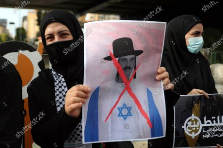 Hezbollah supporter holds a defaced picture depicting Bahrain's King Hamad bin Isa Al Khalifa wearing an Israeli flag, during a protest against normalizing relations with Israel, in Dahiyeh, a southern suburb of Beirut, Lebanon