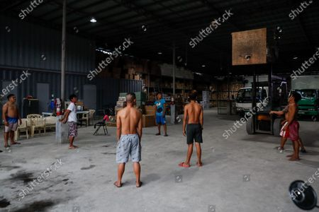 Stock obrázek na téma Filipino workers play basketball with a makeshift ring inside a warehouse amid the coronavirus pandemic in Paranaque, south of Manila, Philippines, 21 September 2020.