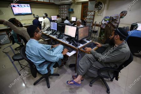 Stock fotografie na téma Stockbrokers monitor the latest share prices during a trading session at the Pakistan Stock Exchange (PSX) in Karachi, Pakistan, 21 September 2020. Benchmark PSX-100 Index was Down 330.63 points during the second trading session in fear over further development of coronavirus COVID-19 cases in the country. Reports state the number of cases infected with coronavirus in Pakistan increased to 450.
