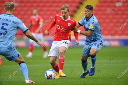 Barnsley's Luke Thomas passes the ball under pressure  Coventry's Gustavo Hamer.