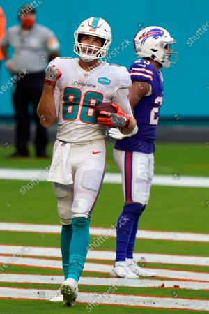 Stock Photo of Miami Dolphins tight end Mike Gesicki (88) celebrates his touchdown during the second half of an NFL football game against the Buffalo Bills, in Miami Gardens, Fla. Against Buffalo the 6-foot-6 Gesicki had eight catches for 130 yards, both career highs