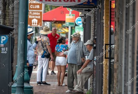 A group of people talk in the middle of the walk side in the Little Havana, in Miami, Florida, USA, 21 September 2020.