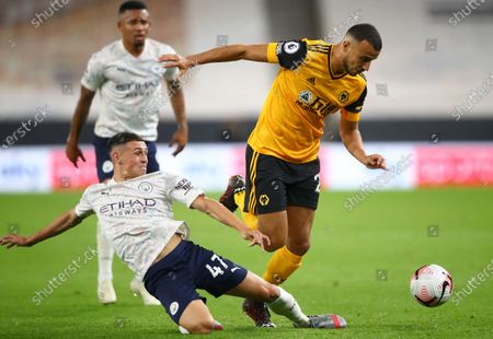 Manchester City's Phil Foden, left, tackles Wolverhampton Wanderers' Romain Saiss during the English Premier League soccer match between Wolverhampton Wanderers and Manchester City at Molineux Stadium in Wolverhampton, England