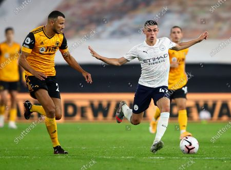 Manchester City's Phil Foden, right, and Wolverhampton Wanderers' Romain Saiss compete for the ball during the English Premier League soccer match between Wolverhampton Wanderers and Manchester City at Molineux Stadium in Wolverhampton, England