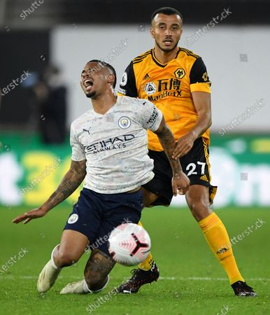 Manchester City's Gabriel Jesus reacts as he is fouled by Wolverhampton Wanderers' Romain Saiss, right, during the English Premier League soccer match between Wolverhampton Wanderers and Manchester City at Molineux Stadium in Wolverhampton, England