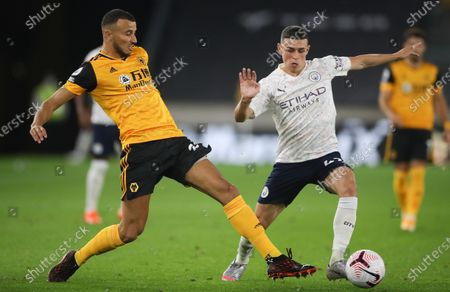 Wolverhampton Wanderers' Romain Saiss, left, challenges Manchester City's Phil Foden during the English Premier League soccer match between Wolverhampton Wanderers and Manchester City at Molineux Stadium in Wolverhampton, England