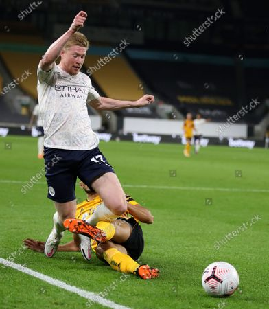 Manchester City's Kevin De Bruyne, left, reacts as he is fouled by Wolverhampton Wanderers' Romain Saiss during the English Premier League soccer match between Wolverhampton Wanderers and Manchester City at Molineux Stadium in Wolverhampton, England