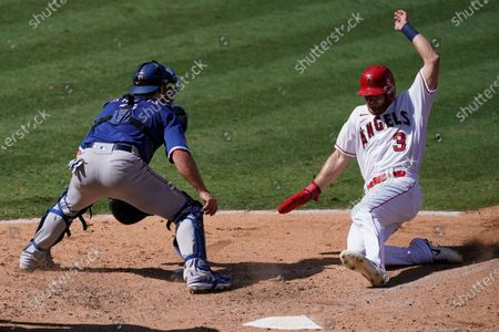 Stock Picture of Los Angeles Angels' Taylor Ward (3) scores after a single by Andrelton Simmons during the fourth inning of a baseball game against the Texas Rangers, in Anaheim, Calif. Rangers catcher Jeff Mathis, left, looks on