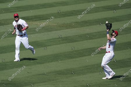 Stock Image of Los Angeles Angels left fielder Taylor Ward, right, catches a ball hit by Texas Rangers' Jeff Mathis for an out during the third inning of their baseball game, in Anaheim, Calif