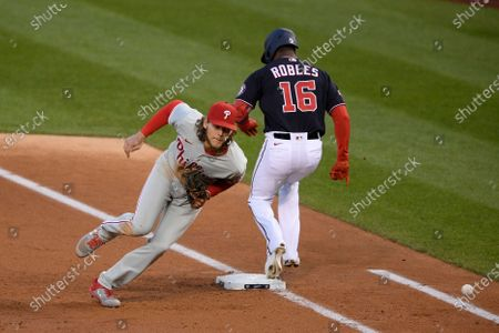 Philadelphia Phillies first baseman Alec Bohm, left, chases the ball as Washington Nationals' Victor Robles (16) singled during the second inning of a baseball game, in Washington. Robles went to second on a throwing error by Phillies starting pitcher Zack Wheeler