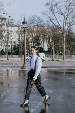 Yoyo Cao attends the Chanel show wearing a white shirt with ruffled collar, Chanel suspenders, navy blue pants, mini bag by Chanel and shoes from Prada outside Chanel, during Paris Fashion Week - Womenswear Fall/Winter 2020/2021