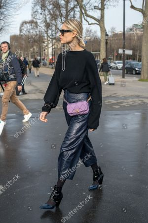 Linda Tol wears Chanel dark blue leather cropped troussers, a Loulou Studio jumper, TOL sunglasses, pointy shiny shoes and a mauve belt bag outside Chanel, during Paris Fashion Week - Womenswear Fall/Winter 2020/2021