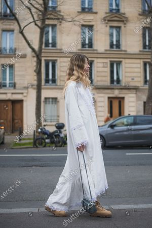 Veronika Heilbrunner wears a long white Loewe dress with a decorative lace edging outside Loewe, during Paris Fashion Week - Womenswear Fall/Winter 2020/2021