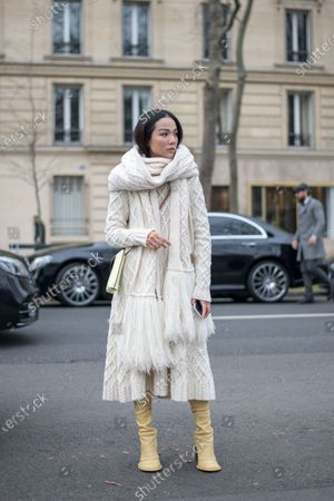 Yoyo Cao wears an off-white knit dress in cashemere with a cable knit bolero and mustard-yellow slouch heeled boots outside the Loewe show during Paris Fashion Week Womenswear Fall/Winter 2020/2021