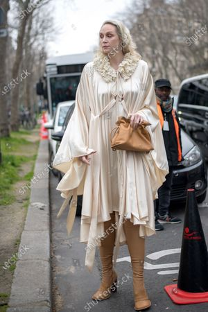 Gwendoline Christie wears a satin dress, a cape with a knit crochet collar detail, loafer-inspired over the knee boots and a bag outside the Loewe show during Paris Fashion Week Womenswear Fall/Winter 2020/2021