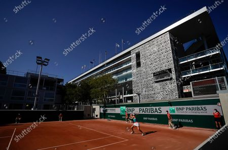 Stock Photo of Harriet Dart returns a back hand under the shadow of Phillipe Chatrier court