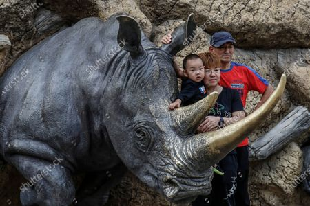 People pose for photo with a rhino sculpture at Beijing zoo in Beijing, China, 22 September 2020. China's leading animal protection organizations on 22 September sent an open letter to President Xi Jingping urging the Chinese government to make China the first country in Asia to ban the import of rhino hunting trophies as the World marks the Rhino Day.