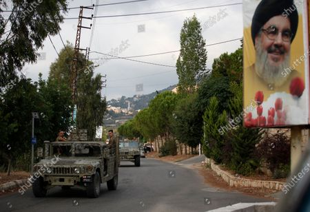 Lebanese army vehicles pass next to a portrait of Hezbollah leader Sayyed Hassan Nasrallah, as they patrol on a road that leads to the site of an explosion that rocked a Hezbollah stronghold, in the southern village of Ain Qana, Lebanon, . The powerful explosion sent thick grey smoke billowing over the village, but the cause was not clear