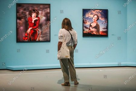 A visitor stands between the artworks entitled 'Untitled 567 2016' (R) and 'Untitled 585, 2018', by US artist Cindy Sherman during the exhibition 'Cindy Sherman at Fondation Louis Vuitton' held at the Louis Vuitton Foundation in Paris, France, 22 September 2020. The exhibition running from 23 September 2020 to 03 January 2021 brings together some 170 works by the artist, produced between 1975 and 2020. After being closed because of the health crisis sparked by the COVID-19 pandemic, The Fondation Louis Vuitton will reopen to the public from 23 September 2020.