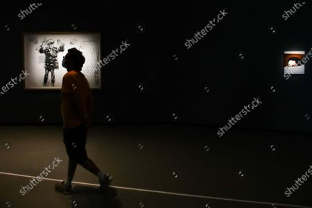 Stock Image of A visitor walks past some artworks by Algerian contemporary artist Adel Abdessemed, during the exhibition 'Cindy Sherman at Fondation Louis Vuitton' held at the Louis Vuitton Foundation in Paris, France, 22 September 2020. The exhibition running from 23 September 2020 to 03 January 2021 brings together some 170 works by the artist, produced between 1975 and 2020. After being closed because of the health crisis sparked by the COVID-19 pandemic, The Fondation Louis Vuitton will reopen to the public from 23 September 2020.