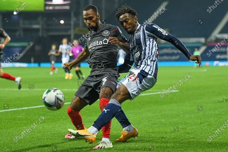 West Bromwich Albion striker Kyle Edwards (21) gets a cross away under pressure from Brentford FC defender Rico Henry (3) during the EFL Cup match between West Bromwich Albion and Brentford at The Hawthorns, West Bromwich