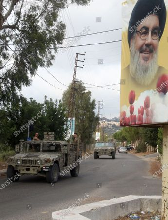 Stock Image of Lebanese army convoy patrols drive near a poster depicting Lebanese Hezbollah leader Sayyed Hassan Nasrallah at the entrance of the village of Ain Qana village, south Lebanon, 22 September 2020. The military declares the site in Ain Qana a closed zone. According to local media reports, that the blast in the arms depot for Hezbollah was caused by a 'technical error'.