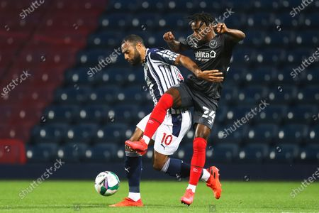 West Bromwich Albion's Matt Phillips, left, and Brentford's Tariqe Fosu-Henry, right, challenge for the ball during their English League Cup soccer match between West Bromwich Albion and FC Brentford in West Bromwich, England