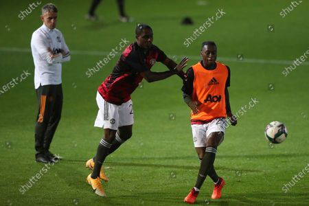 Manchester United's Aaron Wan-Bissaka, right, and Manchester United's Odion Ighalo warm up ahead of the English League Cup 3rd round soccer match between Luton Town and Manchester United, at Kenilworth Road in Luton, England