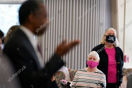 Local residents listen to Housing and Urban Development Secretary Ben Carson, left, speak to reporters after his tour of the Plymouth Place senior housing facility with Iowa Gov. Kim Reynolds, in Des Moines, Iowa