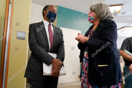 Housing and Urban Development Secretary Ben Carson talks with resident Pam Sokolowski, right, after touring the Plymouth Place senior housing facility with Iowa Gov. Kim Reynolds, in Des Moines, Iowa