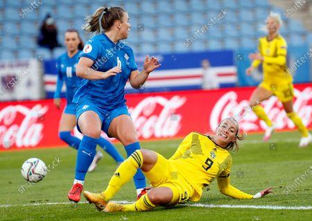 Iceland's Ingibjorg Sigurdardottir, left, challenges Sweden's Kosovare Asllani, right, during the Women's Euro 2021 qualifying soccer match between Iceland and Sweden in Reykjavik, Iceland