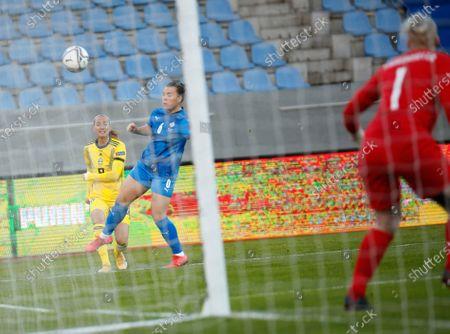 Sweden's Kosovare Asllani, left, crosses during the Women's Euro 2021 qualifying soccer match between Iceland and Sweden in Reykjavik, Iceland