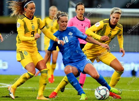 Iceland's Dagny Brynjarsdottir, centre, controls the ball against Sweden's Kosovare Asllani, left, and Lina Hurtig, right, during the Women's Euro 2021 qualifying soccer match between Iceland and Sweden in Reykjavik, Iceland