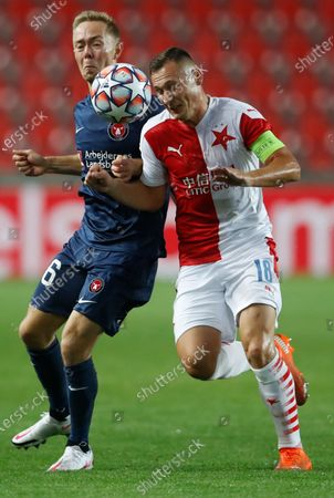 Slavia's Jan Boril, right, challenges Midtjylland's Joel Andersson during their first leg UEFA Champions League play off soccer match between Slavia Praha and FC Midtjylland at the Sinobo stadium in Prague, Czech Republic