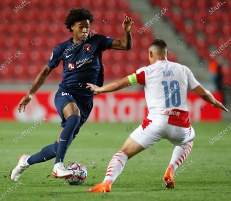 Slavia's Jan Boril, right, challenges Midtjylland's Jens-Lys Cajuste during their first leg UEFA Champions League play off soccer match between Slavia Praha and FC Midtjylland at the Sinobo stadium in Prague, Czech Republic